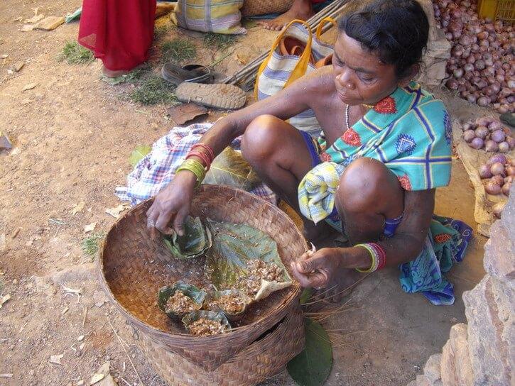Une femme des tribus vendant des fourmis rouges vivantes