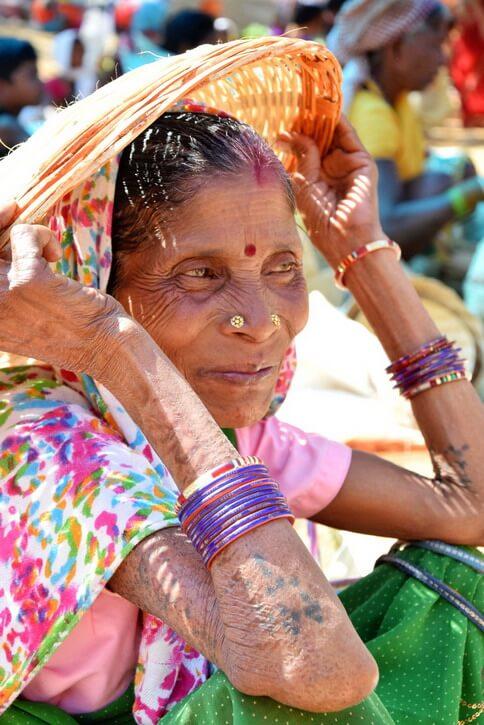 Une femme de la tribu Dhurwa avec des tatouges aux bras et s'abritant sous un panier