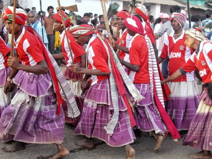 Dhurwa Tribe of Chhattisgarh State in India wearing white and red turbans and long white and purple dresses