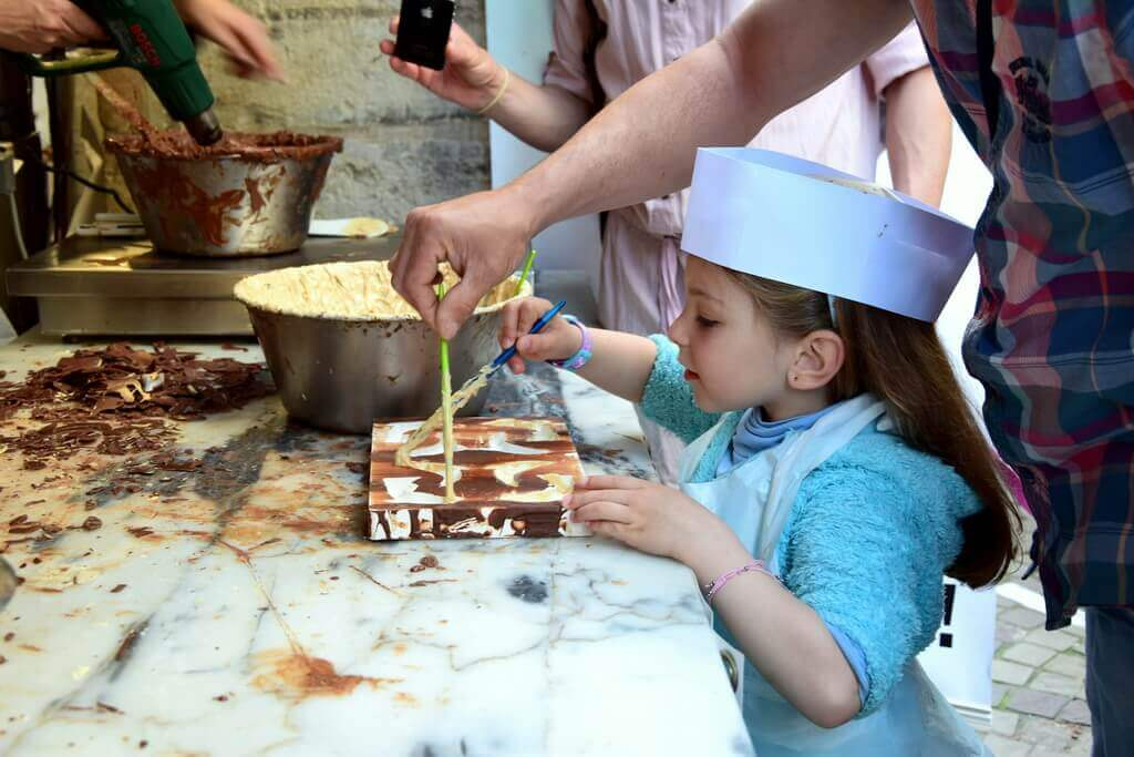A little girl preparing chocolate balls with the help of her parents
