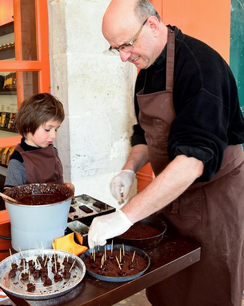 A chocolate Master and his grandson preparing chocolate bites in front of the chocolate factory