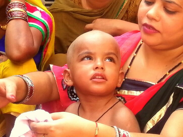 A beautiful little Indian child those hair have just been shaved for one of the traditional life rituals in hinduism, mundan