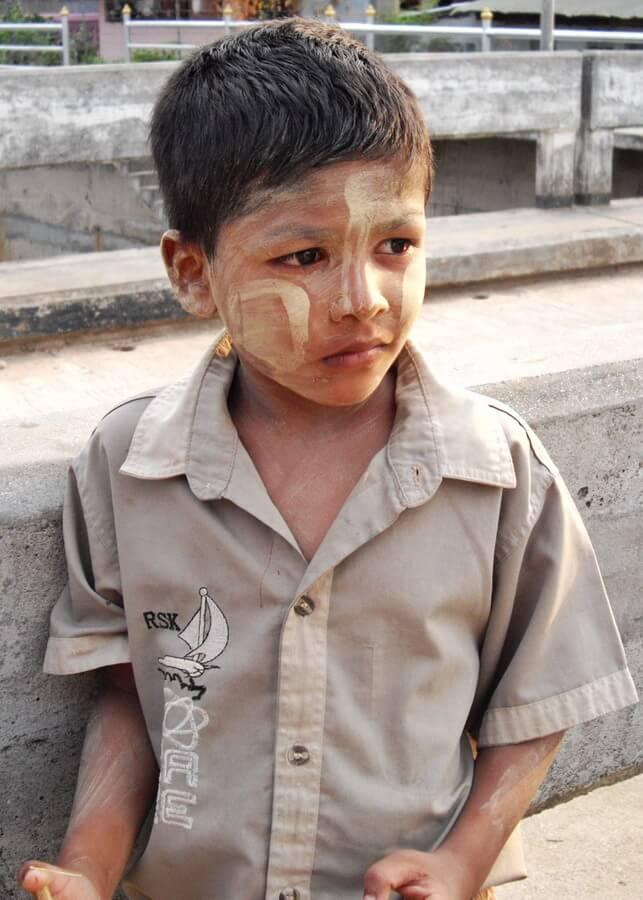 Jeune garçon de Birmanie avec du thanaka sur les joues et le front