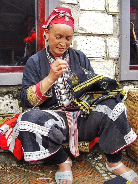 A red Dao woman wearing the traditional clothes and doing handicraft