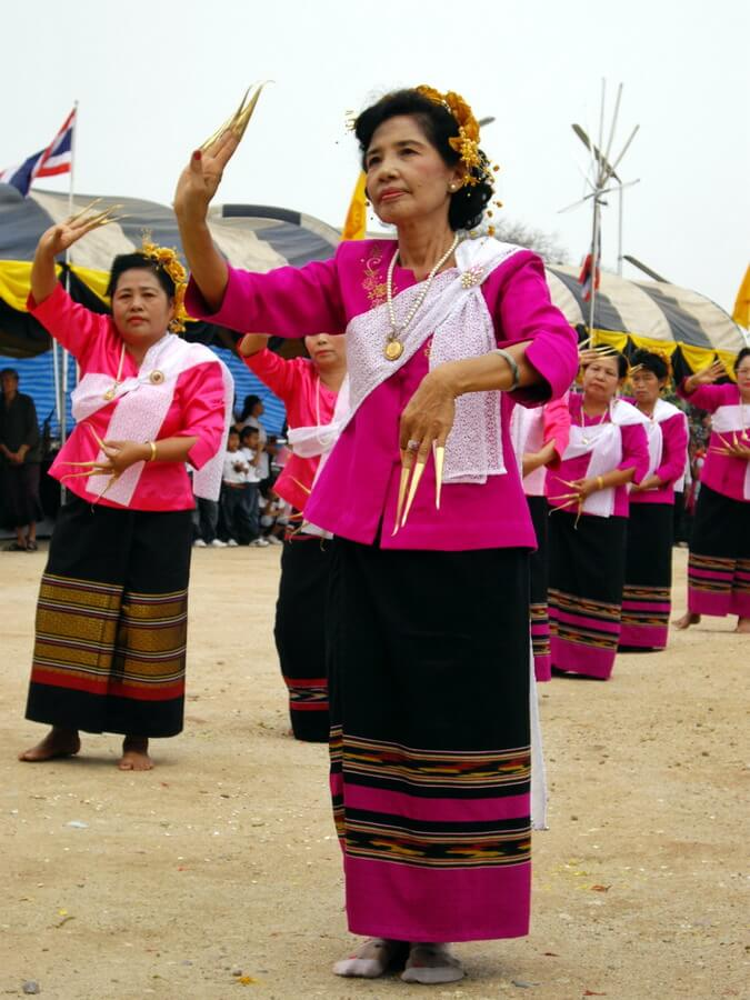 Female dancers wearing a black and pink batik, a pink jacket and long golden nails