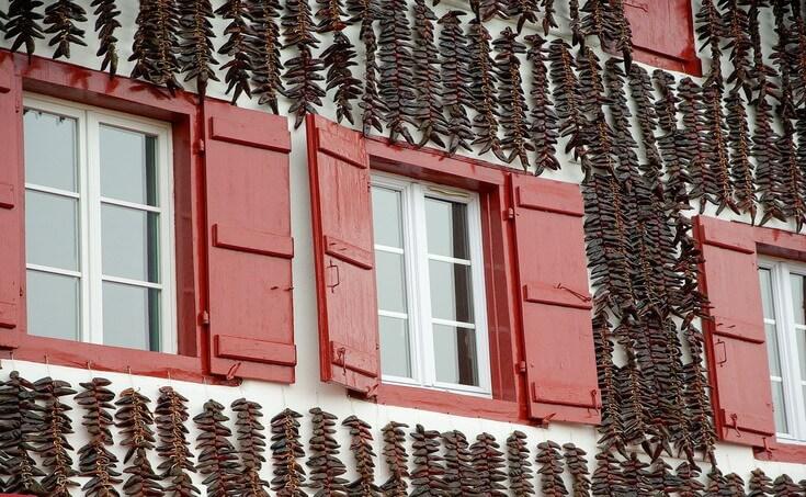 Façade de maison recouverte de tresses de piments d'Espelette, patrie de l'axoa