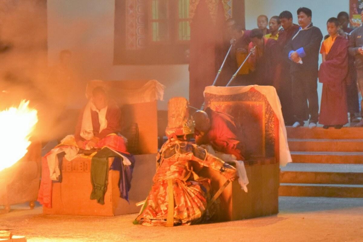 L'oracle bouddhiste tibétain de Dirang accroupi face à un Lama
