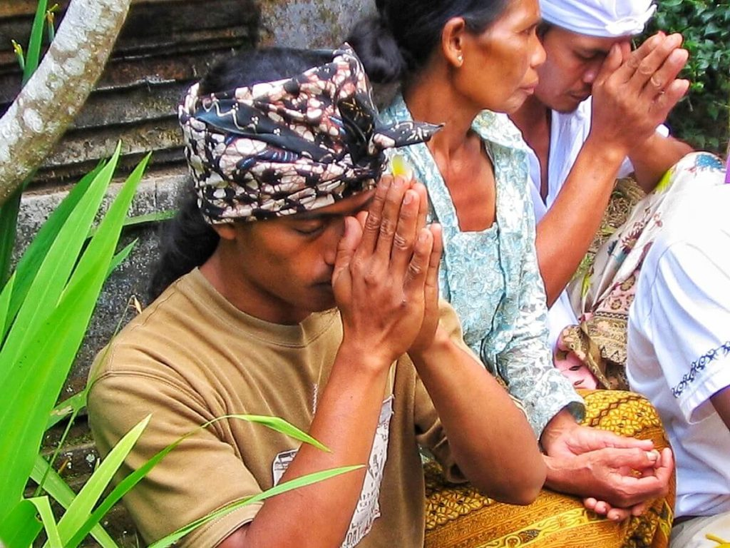 My Balinese friend Ketut praying in the temple before the tooth filling of his wife