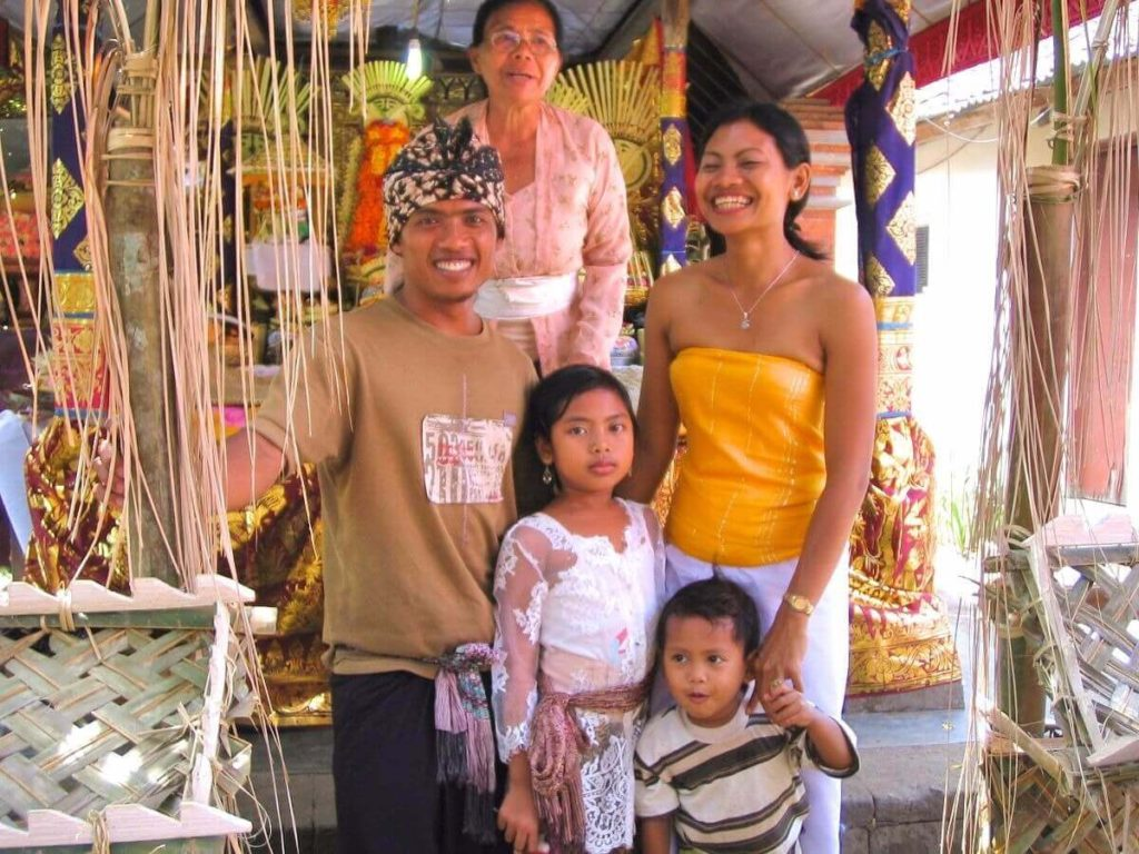 A Balinese couple wearing traditional attires posing with their two children