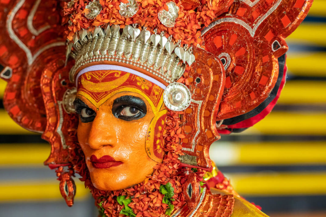 Face of a Theyyam actor with orange, black and red make-up