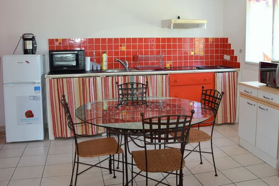 the white, orange and brown kitchen and dinning room