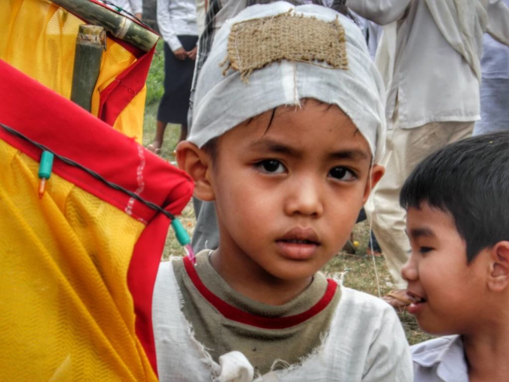 Little boy wearing a white funeral cap