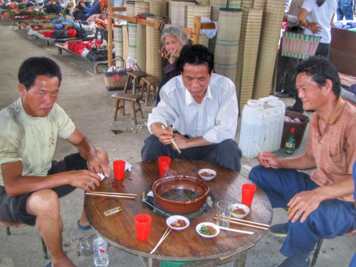 3 Chinois assis autour d'une table basse et d'une fondue