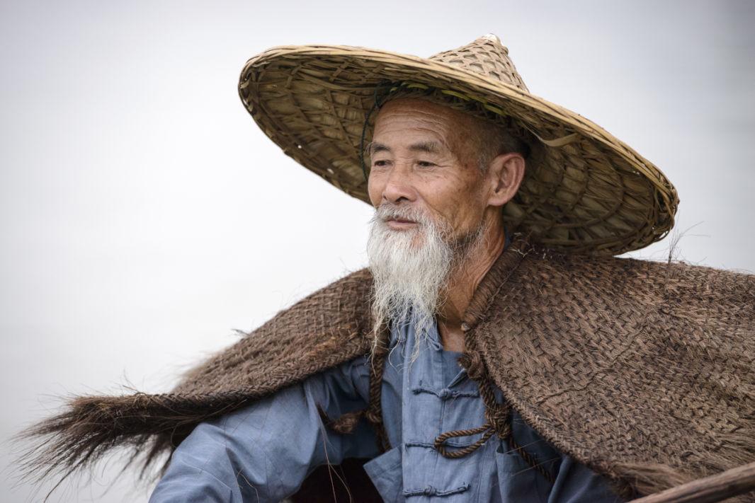 Portrait d'un vieil homme à la barbe et tenue de pêcheur aux cormorans