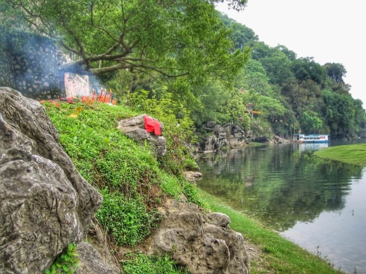 Tombe décorée de pétards et papiers rouges, au bord de la rivière Li