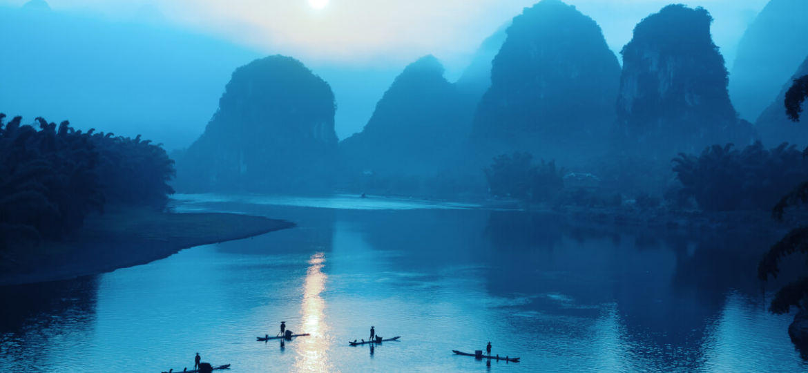 Karst peaks and boats on Li River by night