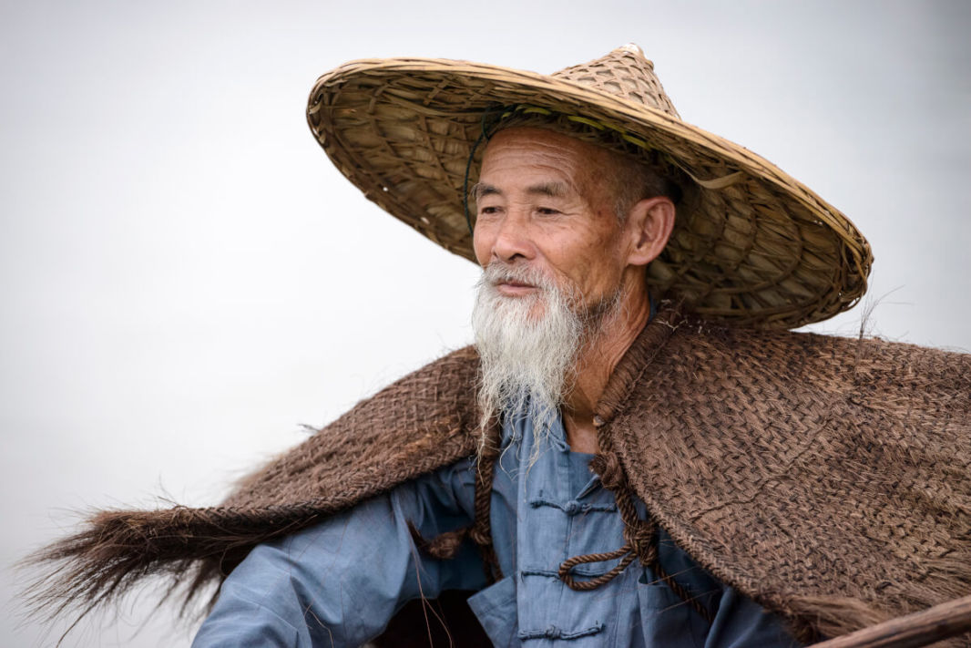 Portrait of an old man with a white Chines-style beard, wearing cormorant fisherman dresses