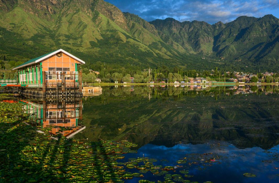 Ponton d'un houseboat avec les montagnes se reflétant dans le lac Dal