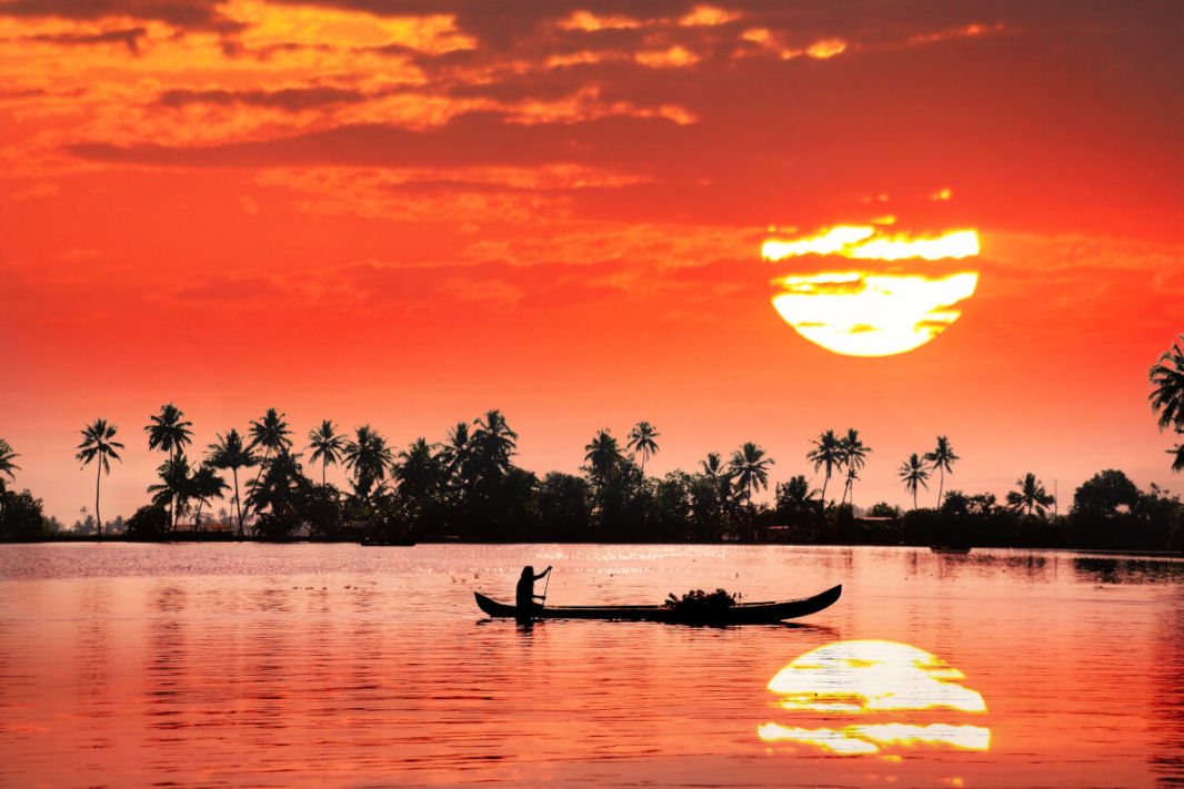 Little boat with Kerala sunset and coconut trees