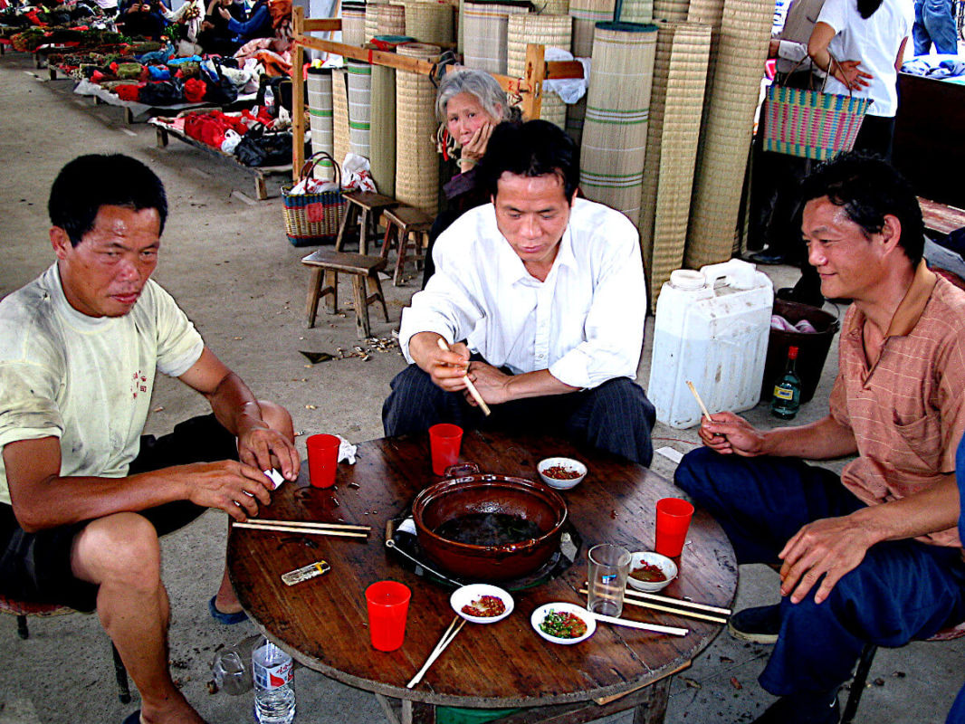 Men eating hot dog pot in Fuli market