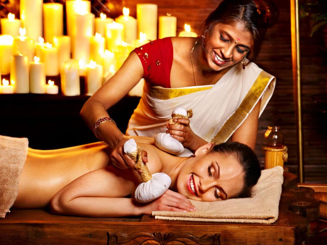 Indienne en saree faisant un massage ayurvédique avec des poches de riz