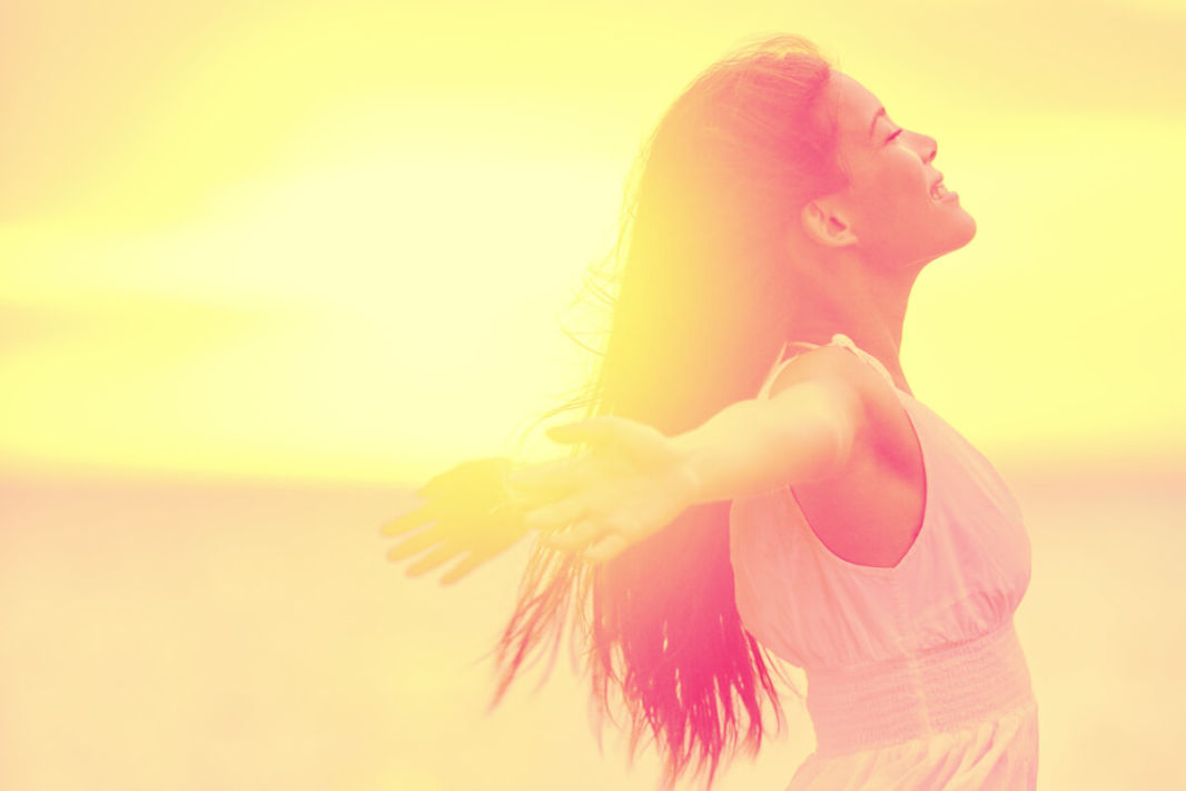 Woman enjoying the sun with wide open arms