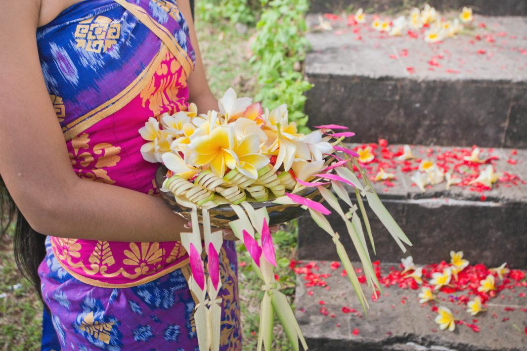 Offrandes de fleurs par une Balinaise en batik