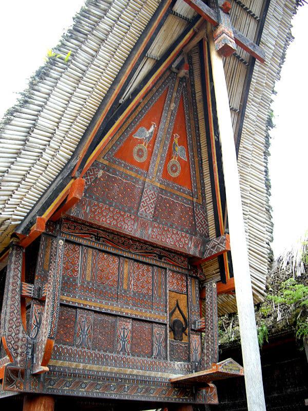 Détail de la façade d'un tongkonan du Tana Toraja, avec peinture orange et motifs animaliers