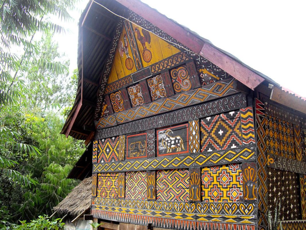 Façade d'un tongkonan orné de coqs, de buffles et de motifs géométriques