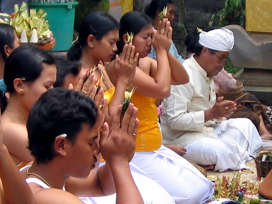 Young Balinese and Balinese priests praying