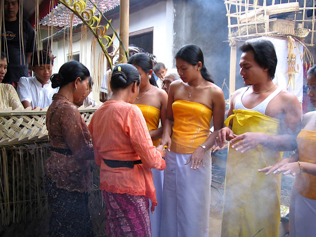 Young Balinese receiving blessing before tooth filling