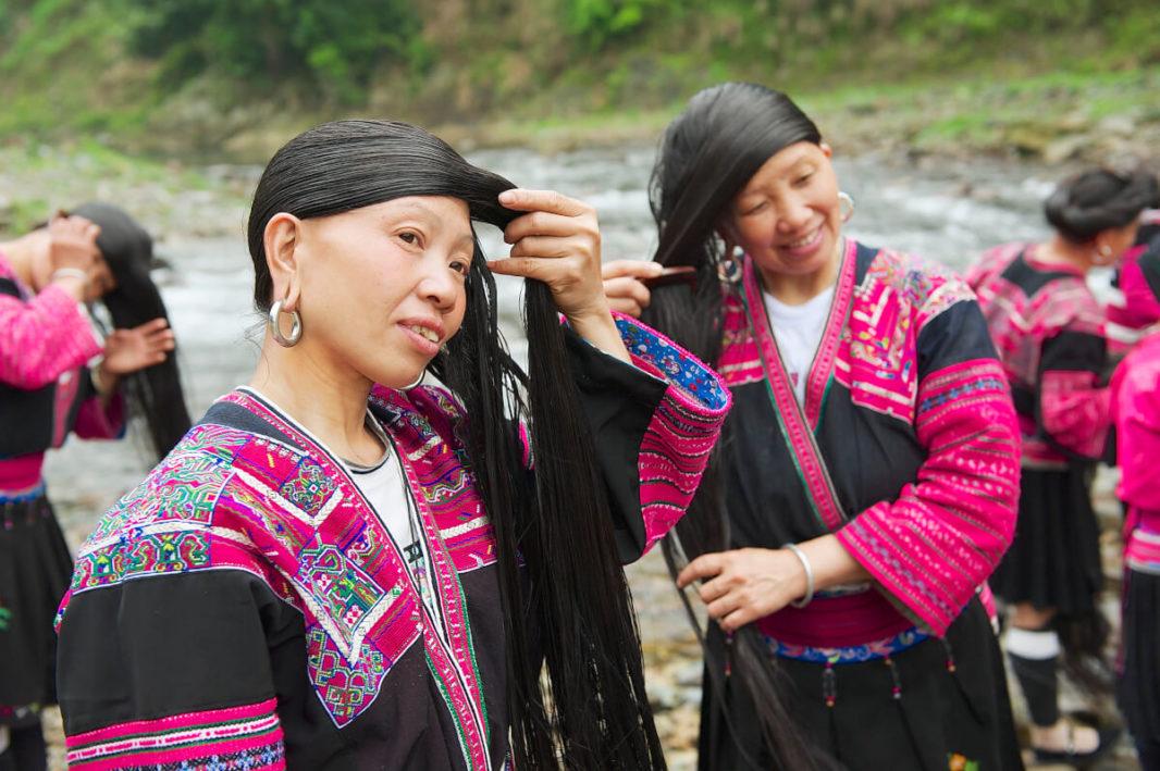 Femmes de l'ethnie Yao Rouge avec leurs longs cheveux dénoués et leur tenue rose et noire