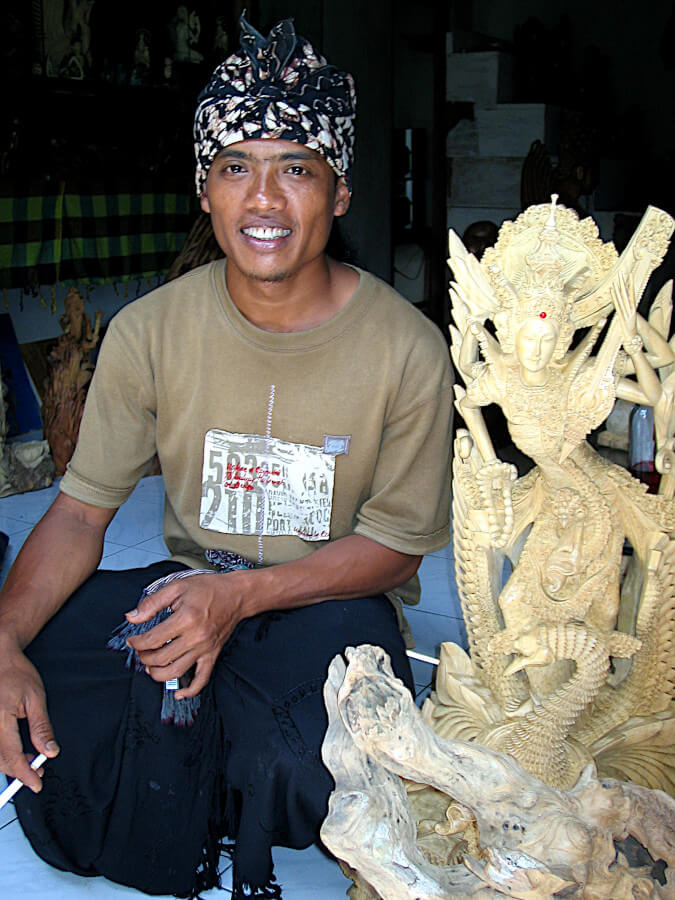 Balinese artist Ketut Sunarta with his Sarawasti sculpture made from crocodile wood