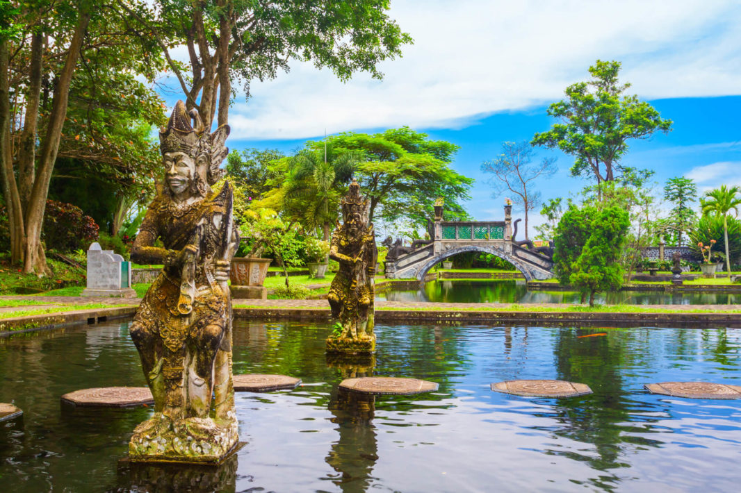 Balinese stone statues on the water, old stone bridge and tropical trees